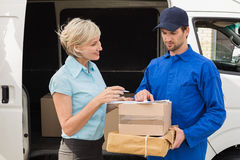 delivery-driver-showing-where-to-sign-to-customer-outside-warehouse-49902000